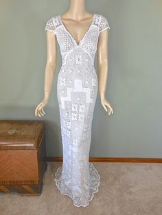 A dramatic, off white, floor length wedding dress made from vintage lace. Stunning, sheer lace, plunging back neckline with scalloped edges.