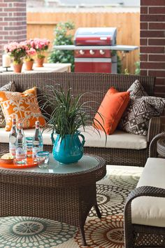 Bright colors, woven textures, pale woods, and a fun medallion outdoor rug help connect this dynamic outdoor space to the interior.
