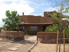 Green adobe home Abiquiu, New Mexico, adobe courtyard walls flanked by stone planters!