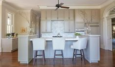 A ceiling fan hangs over a gray kitchen island with end cabinets topped with white marble lined with white leather barstools.