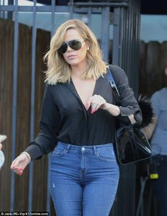Khloe teamed her black blouse with some spray-on blue jeans and showed off her new bobbed locks