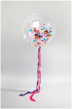 Clear balloons, sprinkle some confetti inside, fill with helium. Takes balloons to a whole new level don't ya think?