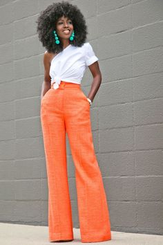 Blusa assimétrica, um só ombro, branca com nó na cintura, calça pantalona laranjada.