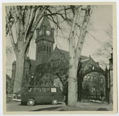 """""""4 College Transportation Service"""" van leaving campus through the main gate of the College, with Mary Lyon Hall in the background :: Archives and Special Collections Digital Images :: circa 1967-1968"""