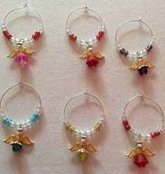 Handmade Angel wine charms. Keep your guardian angel close at all times with this special spiritual gift. Keep your Angel with you while you party. Made with glass beads silver plated fittings and bead spacer and gold colour metal wings. The flower skirt is also glass. Cute little gift or keepsake Only one supplied on each purchase