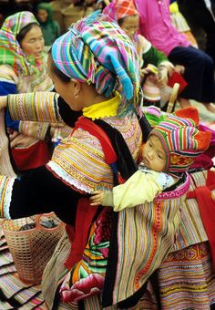 Traditionally dressed Flower Hmong woman with baby in a back carrier, Sunday market, Bac Ha, NW Viet Nam | © Rick Piper