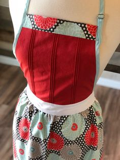 WOMENS PETITE HANDMADE DUAL-PLY APRON This is a dual-ply handmade apron featuring red and white polka dot cotton fabric. This apron has a lovely gathered waistline and extra long ties that measure more than 3 feet on each side. The top of the apron features beautiful hand made pin