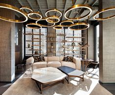 Golden circular suspension lamps for a contemporary style hotel! Feel inspired: www.luxxu.net | #interiordesign #luxuryhotels #lighting
