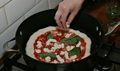 Adding mozzarella to the dry-fried pizza. Photograph: Martin Godwin for the Guardian