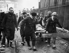 Mrs Bowley, the wife of a school caretaker, shakes the hand of her rescuer, Johnny Driscoll of an A.R.P. rescue team, as she is carried away on a stretcher. Bowley had been trapped in the wreckage of an air raid shelter for thirteen hours after a German bombing raid on London, 17th October 1940.