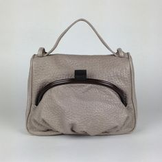 Small leather shoulder bagAlthough small in size this style will give you room enough for your daily essentials. Carry it by the top handle for a ladylike approach, or wear it with the chain over your shouder for a more casual look. Closes with zip on the back. Outside front pocket closes with wooden detail clasp.Fully lined in our signature black and beige cotton. Features phone pocket inside.Detachable metallic handle for a hands-free look.