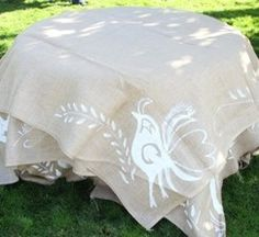 Printed, raw burlap as table cloths? Also, good marketplace to find wedding leftovers.