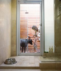 A door in the master bathroom connects the indoor shower to an outdoor one. Here, Feldmann and the couple's three-year-old son, Eli, wash their dog Arnold--named by the previous owner after the local St. Arnold Brewing Company.  Photo by Jack Thompson.
