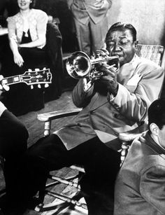 Roy Eldridge plays trumpet during drummer Gene Krupa's jam session at Gjon Mili's studio, 1942.