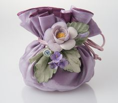 Artistic: Double layer silk sachet filled with almond confetti candies and soft filling, hand made Capodimonte ceramic flower composition.