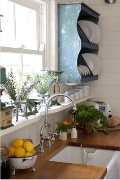 farm house sink, butcher block, and a sink right by the window. perfect. - ledge under cabinets/above counter tops