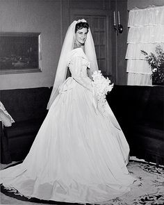 1960 - black and white wedding photo of a young bride in a long-sleeve wedding gown and veil. mid-century wedding dress