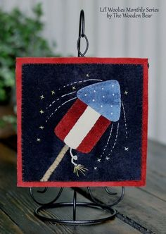 """W07 July Fireworks-by The Wooden Bear. Small hanging on a 7"""" ornament stand."""