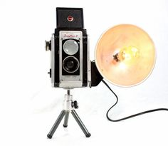 """Vintage Kodak Duaflex II Camera converted into a unique reading lamp mounted on a mini tripod.  Get that vintage look instantly in any room. Has in cord on / off switch. The camera is in excellent condition and just great to look at.  The lamp requires one 7/25/40-watt maximum bulb.  A 7 watt vintage style bulb, classic filament design is included.  Measures 6"""" tall and 8"""" wide."""