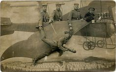The airplane scene seems to have been a fairly common prop in photography studios in the early 1900s.