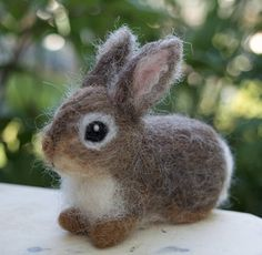 This needle felted young cottontail bunny rabbit was created from a memory of gardening in the spring when I was surprised by baby rabbits eating my ornamental grass. This bunny is needle felted of a variety of natural, undyed wool as well as some dyed wool. The bunny stands about