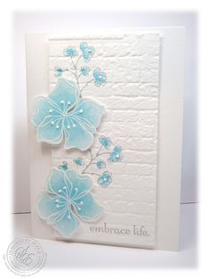 light and beautiful handcraffted card ... white embossed flowers colored in pale blue ... like the small dots of perfect pearls on the flower ... old brick embossing folder texture on panel that is slightly popped from the base card ... beautiful ...