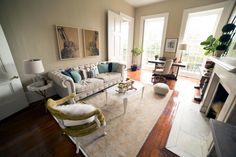 A large floor space leaves room to create extra lounge areas in this lovely contemporary living room filled with vintage charm. Comfy sofa pillows can be piled on top of a large, soft rug for cozy floor seating that makes sense in this boho style space.