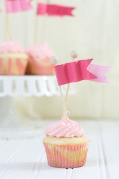 Wavy flag cupcake toppers made out of colored cardstock paper, lollipop sticks,Mod Podge, and wooden dowels