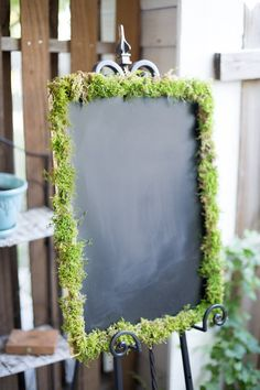 Make a moss frame around a slice of a tree stump painted with chalkboard paint. Gives it a bit more woodsy feel.