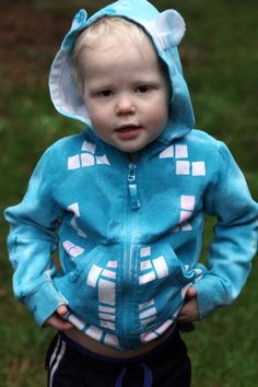 Use masking tape to make a geometric pattern on a stained sweatshirt, then paint with fabric spray paint
