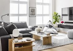 Cozy loft living space with large windows, a gray sectional, and bean bags