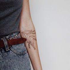 Great and stylish forearm tattoo of a brown floral branch.