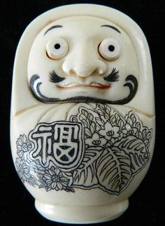 ♥ A Japanese ivory Dharma novelty netsuke with popping eyes, carved from a solid oval piece of tusk. His broad nose balance with a moustache &...