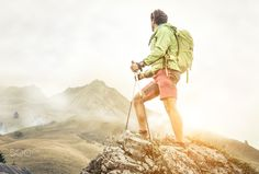 hiker climbing on the mountains. he stays on the top of a rock and watch his…