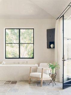 House Tour: Southern California Modern Home Beige Bathroom, Bathroom Interior, Chair In Bathroom, Relaxing Bathroom, Simple Bathroom, Master Bathroom, Black Window Frames, Door Frames, Mediterranean Style Homes
