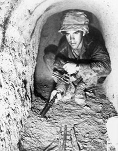 American soldier using a knife to probe the floor of a Viet Cong tunnel in the Iron Triangle north of Saigon, South Vietnam. Jan. 1967.
