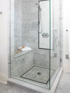 Focal-Point Tile Work: Mix and match tile in your shower to create a design focal point—especially if you are installing glass doors that will allow the tile to be seen from anywhere in the bath. This shower includes two frames of dark tiles around the showerhead and on the floor, which stand out from the surrounding stone tiles and attract the eye | bhg.com