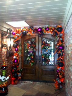 Tutorial on how to decorate with bright orange Halloween garland with pops of purple, welcomes ghost and goblins to stop by for a treat!