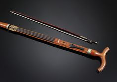 Violin Walking Stick  Disassemble the shaft of this incredibly rare and unassuming walking stick to reveal a working violin. The bow is stored inside the stick, and is accessible when the curved handle is removed. Beautifully crafted and in flawless condition, this cane is an exceptional example of rare musical canes.