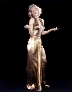 Marilyn monroe usando un vestido de color dorado y levantando los brazos