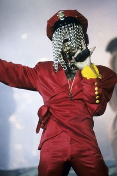 He delivers a powerful performance at Radio City Music Hall in NYC in 1993, wearing a wrap-front red suit and a police cap with a chain curtain obscuring his face.  #refinery29 http://www.refinery29.com/2016/04/108919/prince-fashion-outfits-style#slide-10