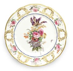 A fine Nantgarw plate, circa 1818-20 Painted in London in the Bradley workshop with a spray of flowers including a 'divergent' tulip, pink roses and an auricula, an insect in flight to one side, the cavetto picked out in blue enamel, the C-scroll border painted with roses and a comical bird, the moulded wreaths picked out in gold,