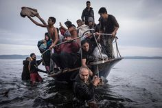 Migrants arriving in Greece on a Turkish boat, whose owner was later arrested in Turkish waters.  The Year in Pictures 2015 - The New York Times