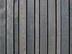Black stained vertical wood board siding. In the project Erf Overmeen in Heeten, Netherlands, designed by Happel Cornellisse Verhoeven. Photography courtesy of Happel Cornellisse Verhoeven.