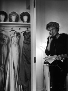 Singer Julie Wilson on Phone Beside Closet with Hanging Evening Dresses and Wigs on Top Shelf Premium Photographic Print by Nina Leen at Art.com