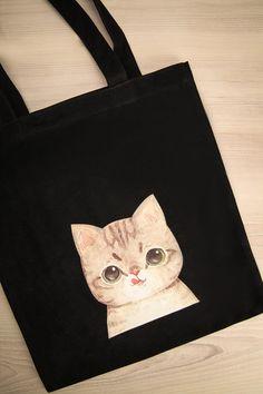 Son mignon chat espiègle la regardait avec de grands yeux.  Her cute and mischievous cat was looking at her with its big eyes. Girisma - Black cat-print tote bag www.1861.ca