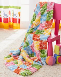 Made up of multicolored knit blocks, this blanket is perfect for brightening up any nursery. Knit in Bernat Tizzy.
