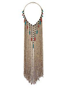 De largo Con forma de cascada y con piedras de colores en tono esmeralda y coral, este collar de Topshop puede ser el mejor complemento ante un vestido liso y simple (39 €).