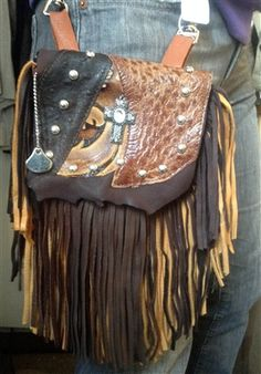 """IRON CROSS - saddle tan deerskin w/ brown & tan deerskin fringe. Features real ostrich & printed leather with centerpiece cross of crystal, silver & stones. All bags transformed from recycled old handbags, vintage jewelry & exotic leather remnants that are wearable works of art. Big enough to hold a phone, cash, ID, & whatever else is a """"must have."""" Small interior pocket holds ID, credit cards & cash. Interior includes a leather strap. Add the strap when you want a completely different look."""
