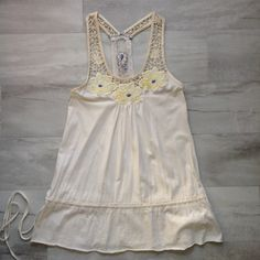 Free People Flowered Tank Beautifully embroidered top from Free People. Cream cotton knit with side tie and skirting detail, yellow & blue embroidered flowers, lace detail on racerback. This has seen some wear, note the photos: small snags/holes in the back on skirting, some threads frayed, small discoloration on from beneath embroidered flowers. Size XS Free People Tops Tank Tops